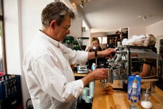 Christoph am historischen Espresso-Zapfautomat in seinem neuen Getränkefeinkostladen
